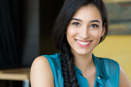 Closeup shot of young woman smiling. Portrait of brunette girl looking at camera and smiling. Shallow depth of field with focus on beautiful young happy girl with braid smiling.